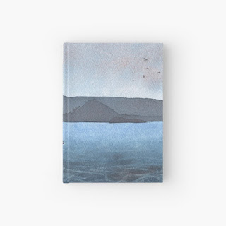 A photo of a hardback notebook featuring a watercolour painting of Berwick Law