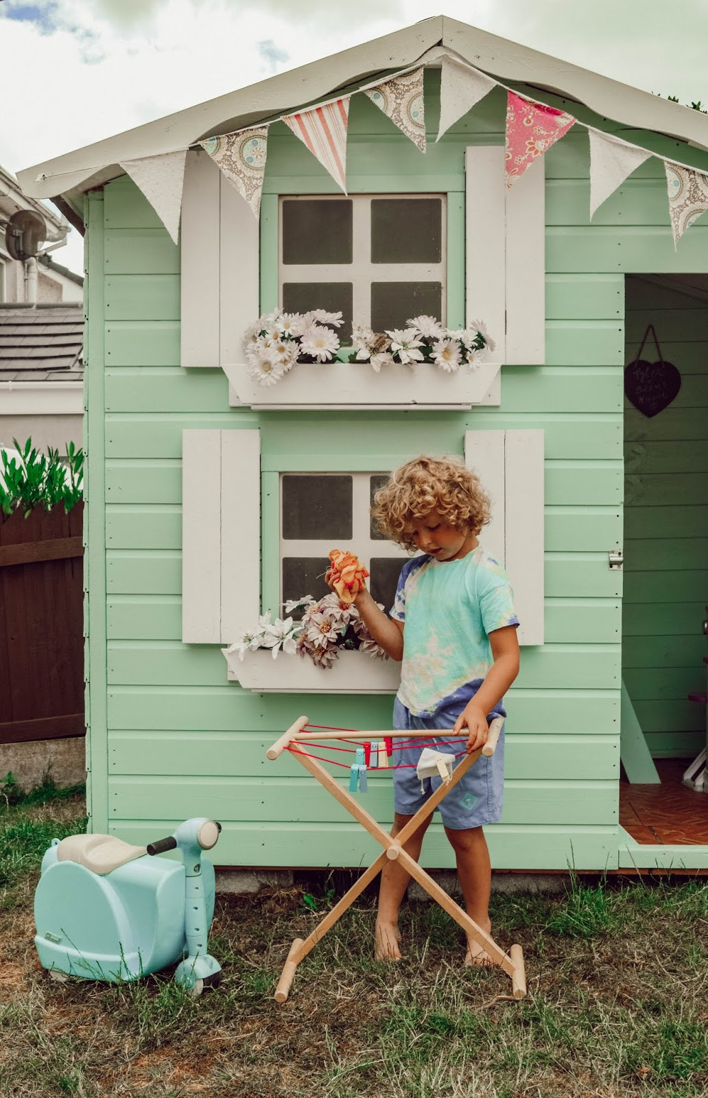 Child playing outside a playhouse