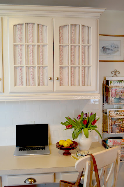 Cottage Style desk area with fabric on glass cabinets