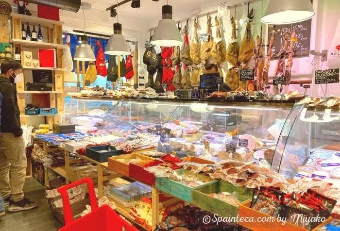 冷蔵ショーケースに並ぶグルメ食材とスペイン人買い物客
