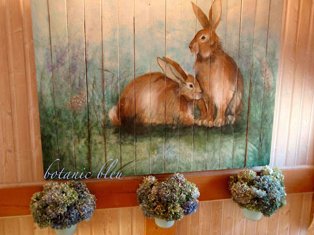 Drying hydrangeas hang beneath hand painted bunnies on wood planks in stairwell