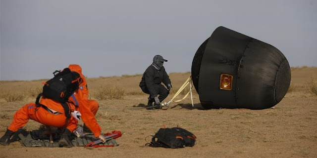 Scientific personnel works at the landing area of the re-entry capsule of China's first retrievable microgravity satellite Shijian 10 in Siziwang Banner, north China's Inner Mongolia Autonomous Region, Apr. 18, 2016. Photo Credit: Xinhua/Chen Junqing