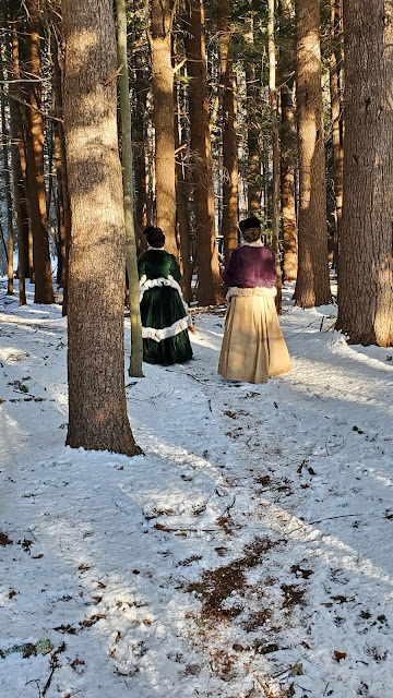 the author and friend in bustle ensembles trekking through a snowy forest