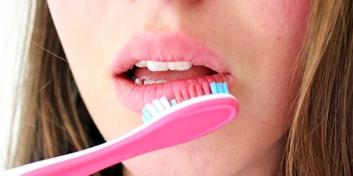 chica exfoliando sus labios con cepillo de dientes rosa