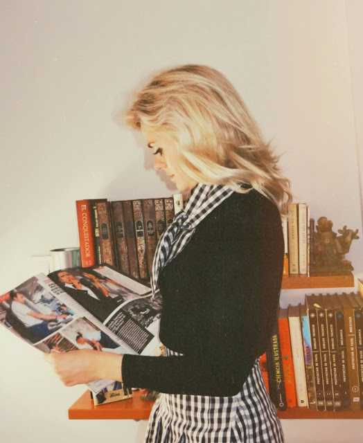 Alejandra Colomera vestida con jersey negro, falda de tablas cuadros vichy y lazo en el cuello vichy leyendo revista Lecturas
