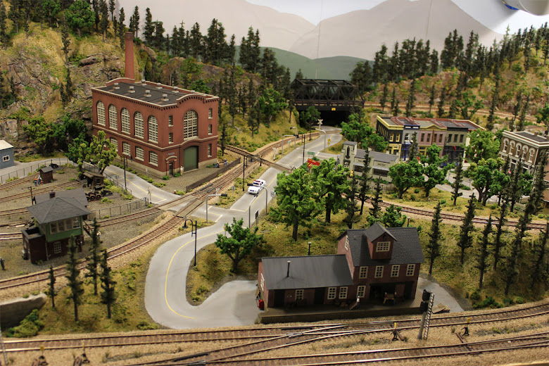 A complete 4 x 8 HO scale model railroad layout with industrial, urban, forest, and mountain scenery