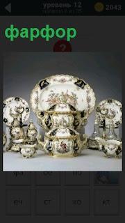 На столе стоят изделия из фарфора чашки, сосуд и тарелка, с красивой роспись на них