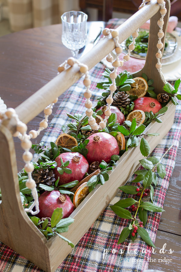 pomegranates and evergreen clippings in wooden toolbox used as centerpiece