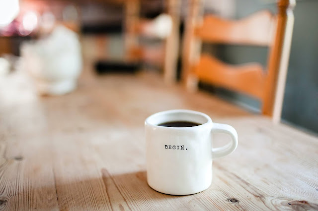 "White mug full of black coffee sitting on wooden dining table. Writing on mug reads, ""Begin""."