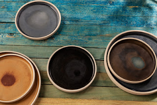 Olympia Canvas crockery on a multi-coloured wooden background