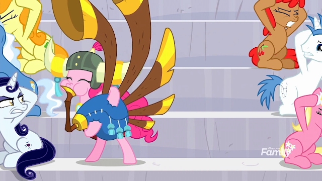 Pinkie playing in some bleachers now wearing a helmet with yak horns and pink tassel. Ponies look on in anger.
