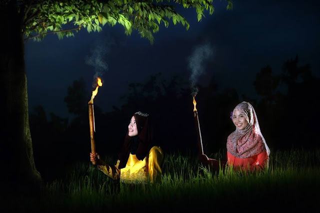 hijab model photogrpahy bawa obor bambu di malam hari ramadhan