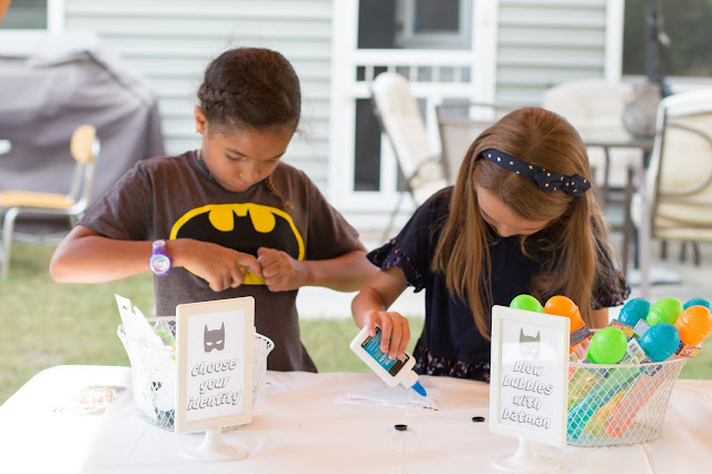 girls decorating a masks at a batman party