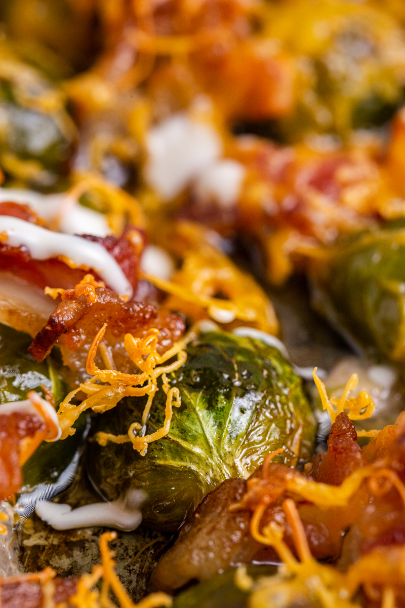 Close up photo of Cheesy Bacon Ranch Brussels Sprouts on a sheet pan.