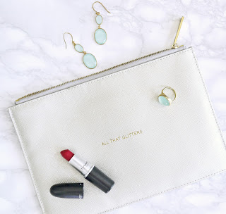 white clutch bag with red lipstick and earing on flat lay