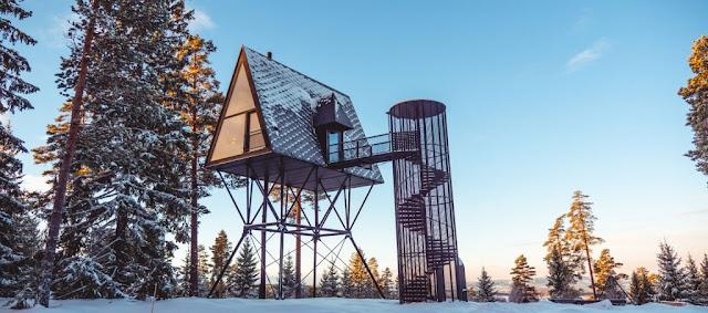 cabaña elevada sobre estructura con nueve en el bosque