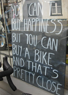 "Handwritten sign in bike shop window, ""You can't buy happiness but you can buy a bike and that's pretty close"", Castle Douglas, Scotland"
