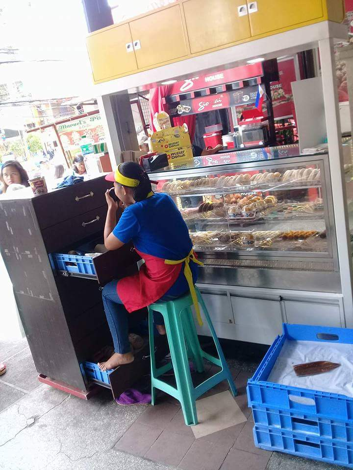 'Tindera' casually rests bare foot on top of a crate of donuts