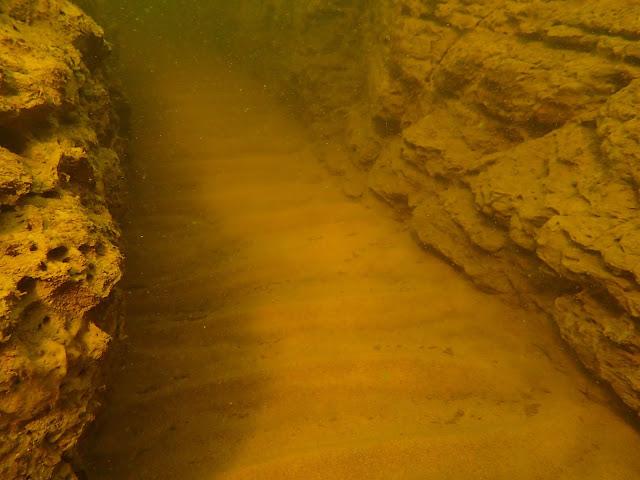 Saviseinämien muodostama kanjoni hiekkapohjalla