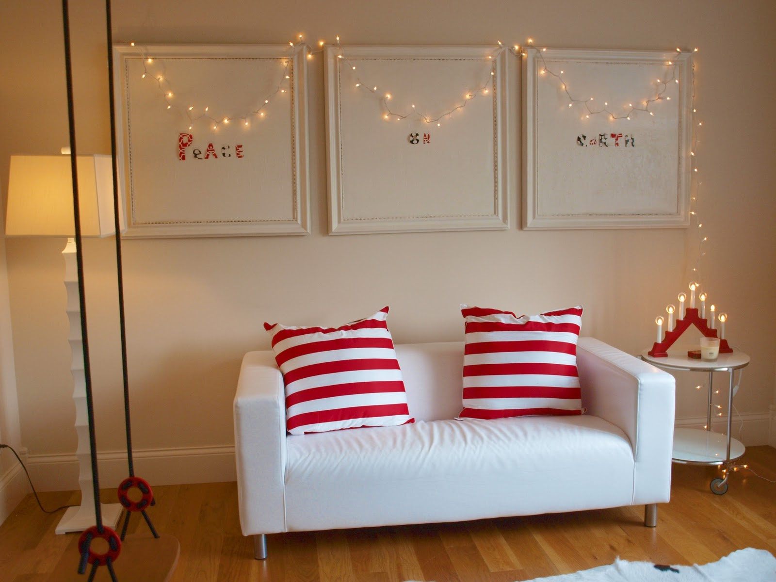 White leather loveseat with red and white stripe pillows in a studio with swing by Hello Lovely Studio