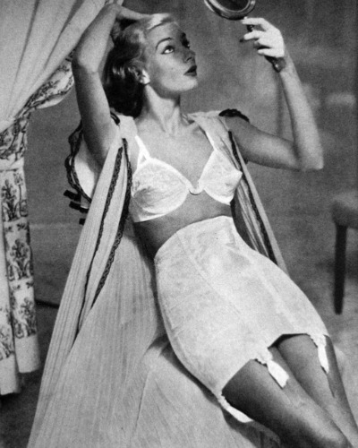Model reclining in 1951 Vogue Ad wearing a bullet bra and open bottom girdle
