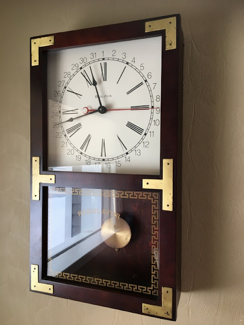 wood and brass clock hanging on a wall.