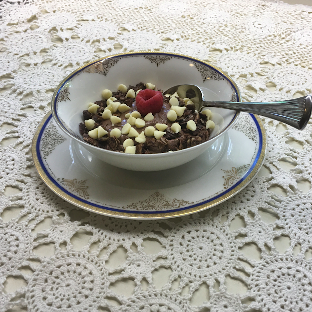 image - bowl of prepared keto chocolate yogurt pudding topped with sugar free granola and white chocolate chips