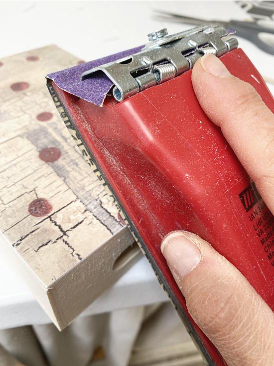 sanding the box using a block sander