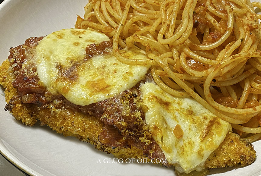 Chicken parmesan on a plate with spaghetti