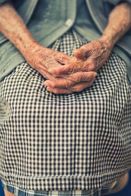 Old woman with hands in lap: Photo by Cristian Newman on Unsplash