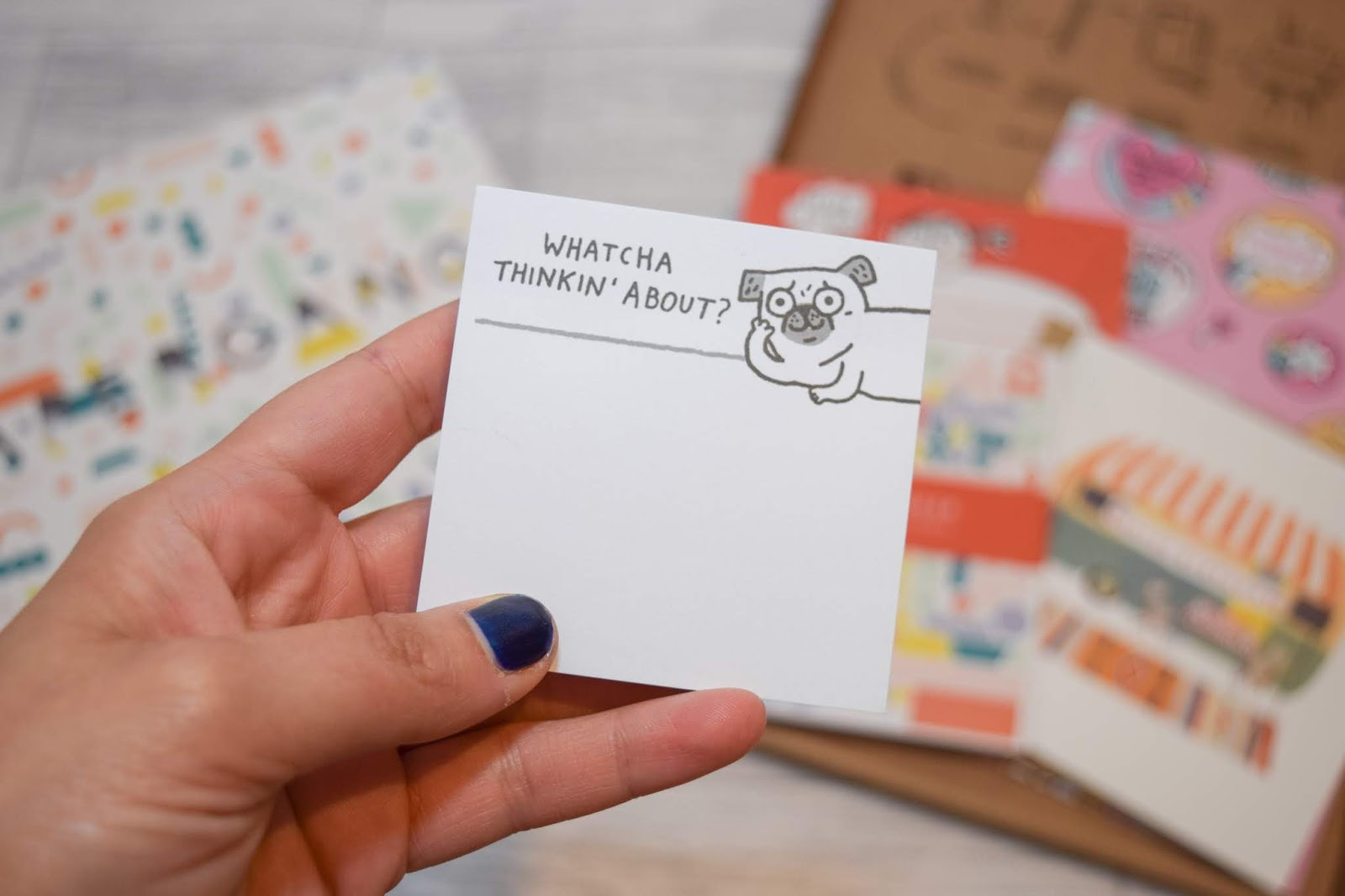 A hand holding post it notes with a dog and the sentence 'whatcha thinking about?'