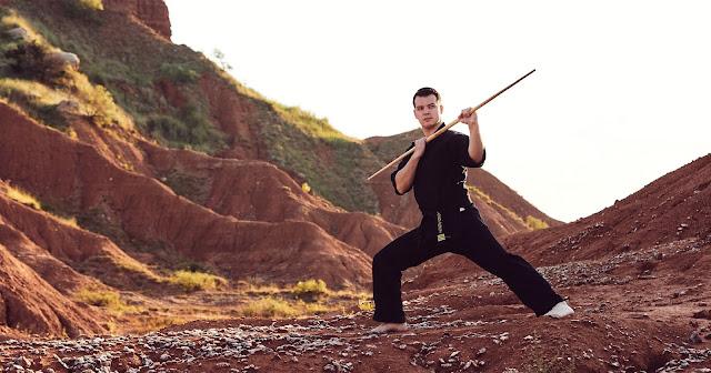 Jackson Rudolph in a mountainous terrain with his bo staff.