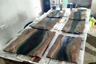 Six river sections all painted and drying on the dining table