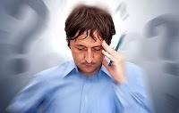 Kalem olan elini kafasına koyup gözleri kapalı düşünürken konsantre olmaya çalışan bir adam