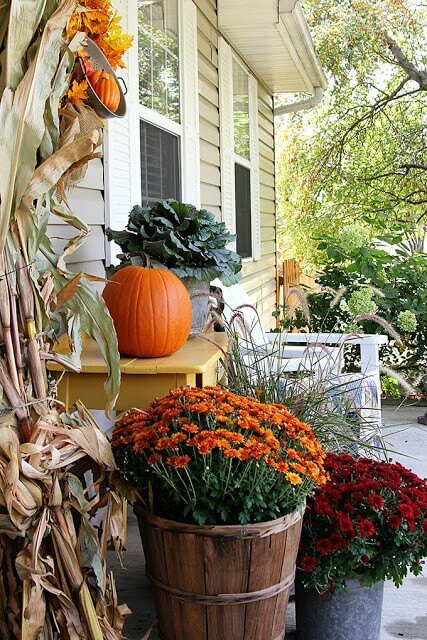 Fall front porch decorated with flower filled tubs and buckets, rocking chairs, pumpkins and cornstalk
