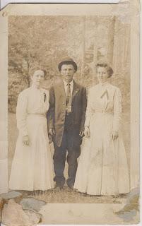 Kuvassa seisoo kaksi naista ja mies. Naisillä on valkoiset vaatteet ja sintapielessä jokin merkki. Miehellä on puku päällä. Puvun housut ovat vähän pitkät ja ovat rypyssä. Hänellä on päässään knallihattu.Tausta on valokuvaamon maisemataustakuva.