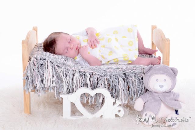 séance photo naissance en famille, photo bébé fille sur petit lit en pin