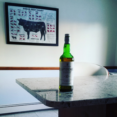 image of my kitchen, with a bottle of Laphroaig sitting on the counter; in the background, an Angus beef chart hangs on the wall