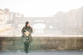 ishita standing on a bridge in florence with the ponte vecchio behind her