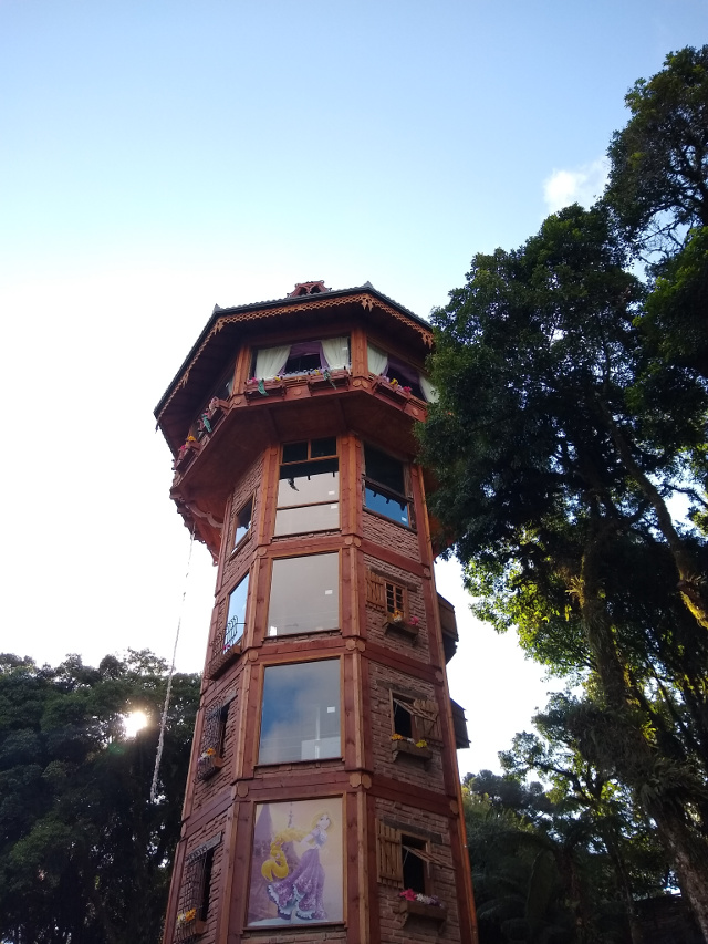 A brown tower with many windows and trees around it;
