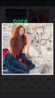 девушка в теплой одежде сидит рядом с оленем у которого красивые рога