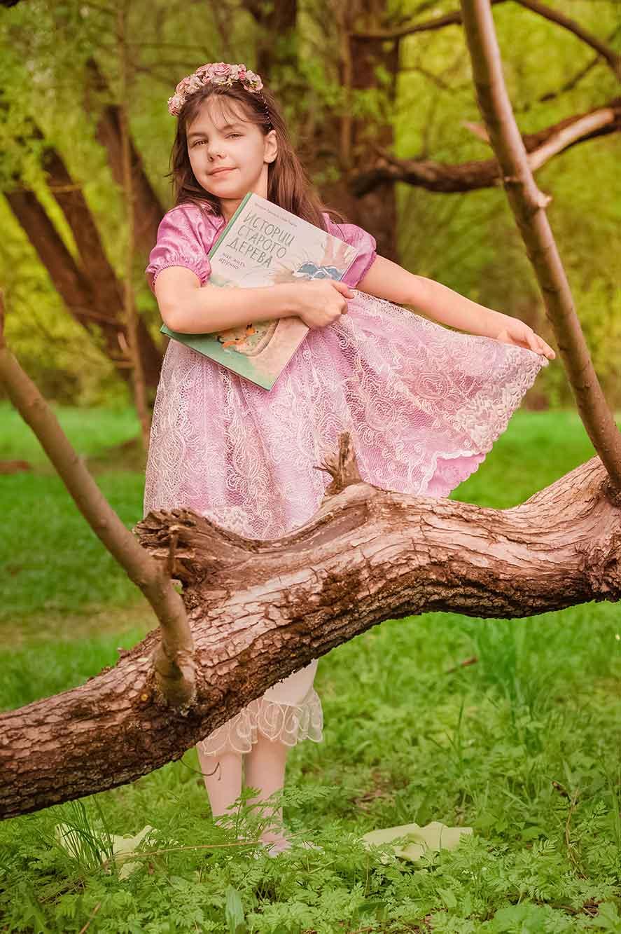 девочка с книгой у дерева