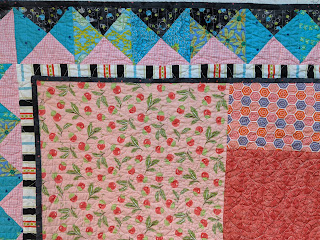 Folded quilt shows the pink, blue, and black hourglass border and the peach fabrics on the back of the Improv Hourglass quilt.