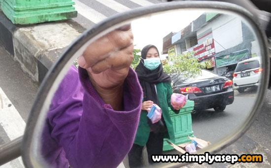 BERBAGI TAKJIL DI JALAN : Terlihat seorang mahasiswi denga kantung kantung Takjil yang dia dan teman temannya bagikan di Lampu merah kawasan Simpang JalanZainudin Pontianak Sabtu (25/4) sekitar pukul 16.14 WIB. Foto Asep Haryono