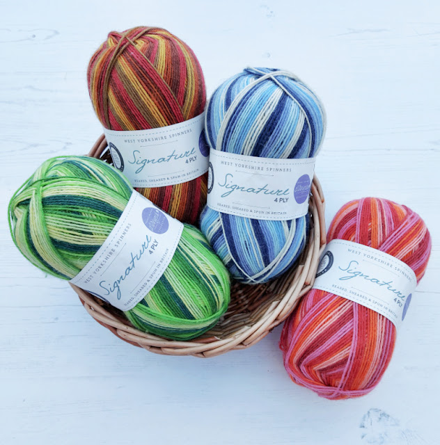 Three balls of yarn in a round wicker basket - one is shades of green, one is shades of brown, one is shades of blue.  A fourth ball in shades of pink lies next to the basket on a wooden floor