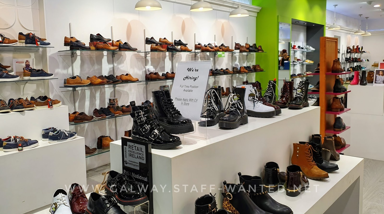 autumnal colour (expecially brown) shoes on display in a city shopping mall shoe shop with white walls and display cabinets and lime-green feature wall  - surrounding a sign advertising for new staff to work in the shoe-shop