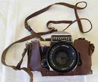 A classic Praktica film camera with leather case and strap.