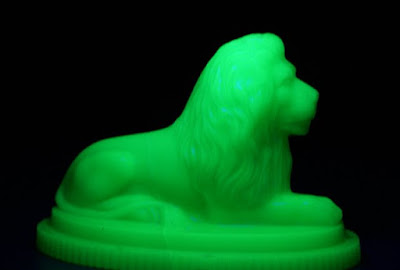 Seated green glass lion paperweight photographed under Ultra Violet light which gives a black background and a green glowing lion.