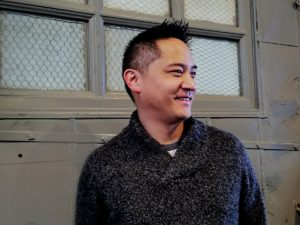 Author Mike Chen wearing a cozy sweater and looking off to the side.