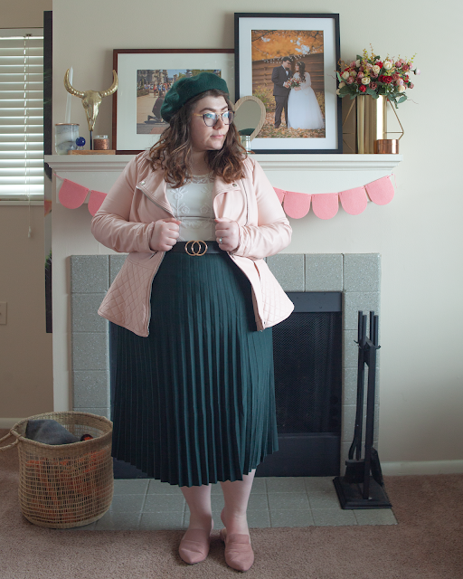 An outfit consisting of a green beret, pastel pink faux leather in a quilted peplum cut over a lace blouse tucked into a forest green pleated midi skirt and dusty pink pointed toe mules.